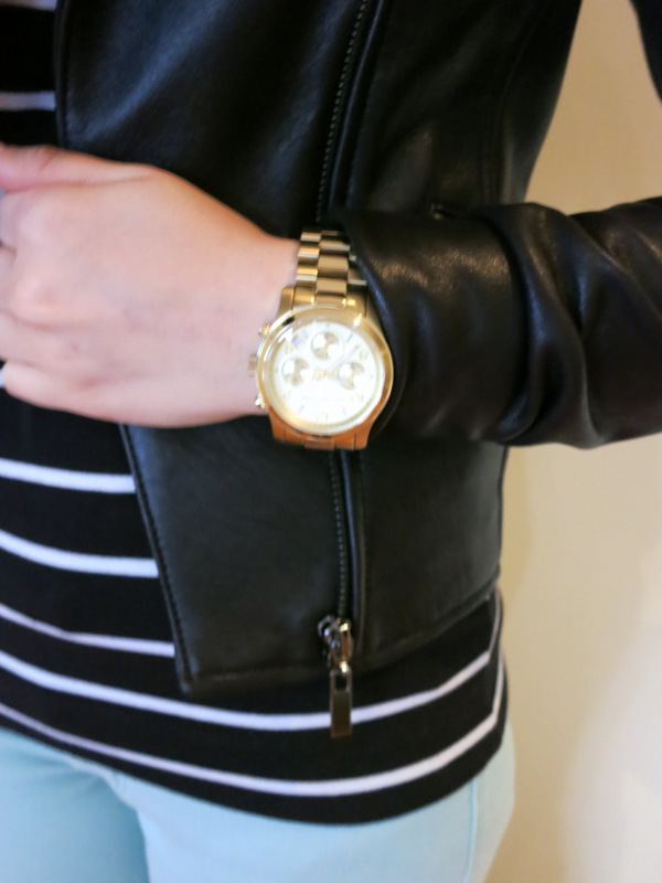 Mint green jeans, black and white striped top, black leather jacket, black boots and gold watch