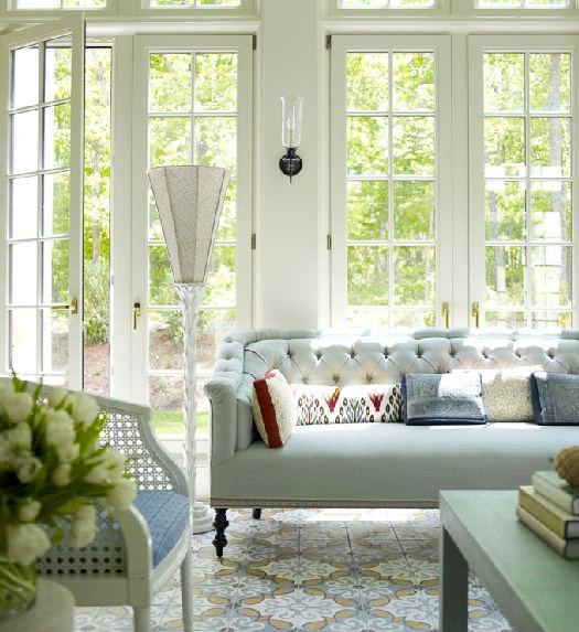 Living room with a tufted mint green sofa, Moroccan inspired patterned rug, a cane chair with a blue cushion, white french doors and a green coffee table in Katie Ridder's home