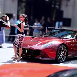 Posing with a Ferrari.