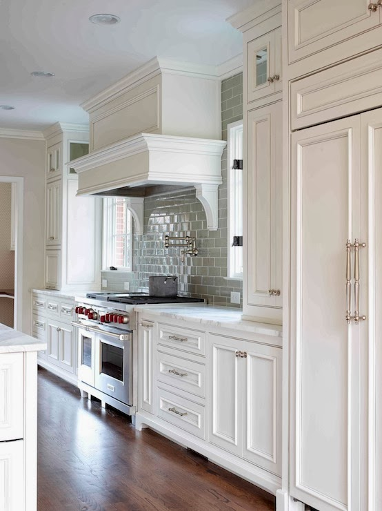white and gray kitchen,  white cabinets,  beaded cabinets,  beaded kitchen cabinets,  white beaded cabinets,  white beaded kitchen cabinets,  gray subway tile,  gray subway tile backsplash,  gray subway tile kitchen , calcutta gold marble,  calcutta gold marble countertop,  paneled kitchen hood,  kitchen hood corbels,  kitchen hood brackets,  double door refrigerator , paneled fridge , paneled refrigerator,  kitchen wood floors