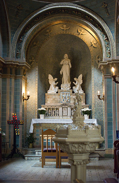 Serene light blue chapel withe image of Our Lady, Mary, at the center flanked by kneeling angles and framed by 7 doves
