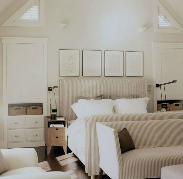 Bedroom with ticking stripe upholstered striped sleigh bed, a matching striped bench, white built in shelves and a wood floor