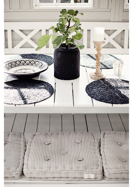 Table setting on a grey front porch with stripped pillows and Moroccan inspired bowls