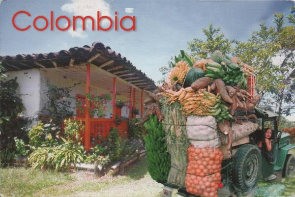 tractor loaded high with fruit and vegetables beside a house veranda with flowers