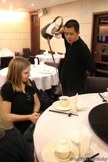 Pouring tea with a teapot with a metre-long spout for Kelly Kilgour, corporate communications executive, Air New Zealand, our tour guide, at 1121, a restaurant photograph