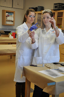 Two women look at a shoe print impression in the lab.