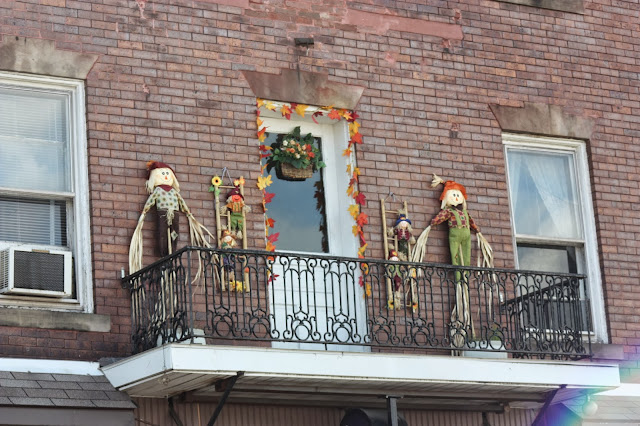 balcony decorated with scarecrows and leaves