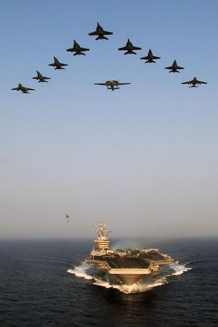 Aircraft from Carrier Air Wing (CVW) 7 fly over the Nimitz-class aircraft carrier USS Dwight D. Eisenhower (CVN 69)