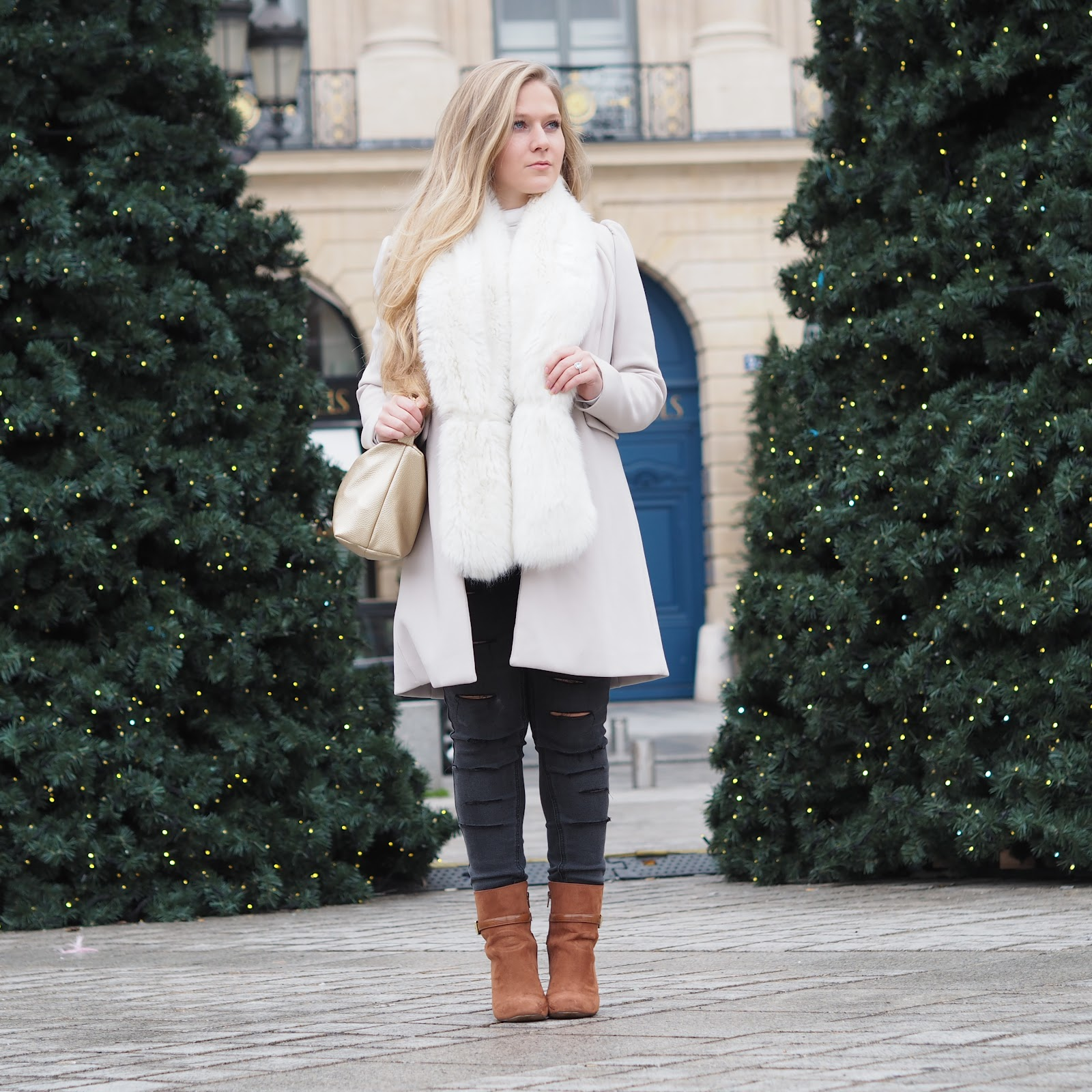 Blonde girl standing between christmas trees in Place de Vendome, Paris