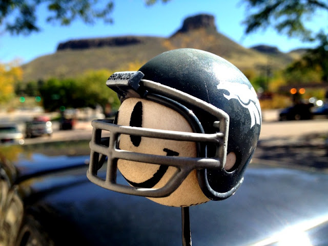 A Denver Broncos helmet on an antenna ball in front of South Table Mesa in Golden, Colorado.