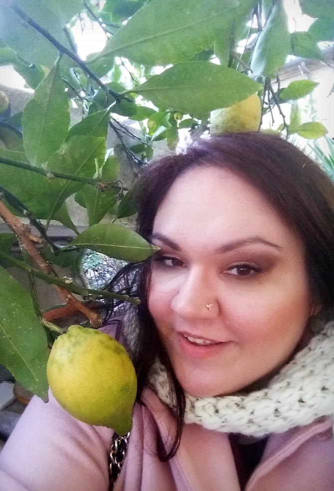 outfit taglie comode con cappotto rosa svasato nel giardino mediterraneo primopiano con limoni