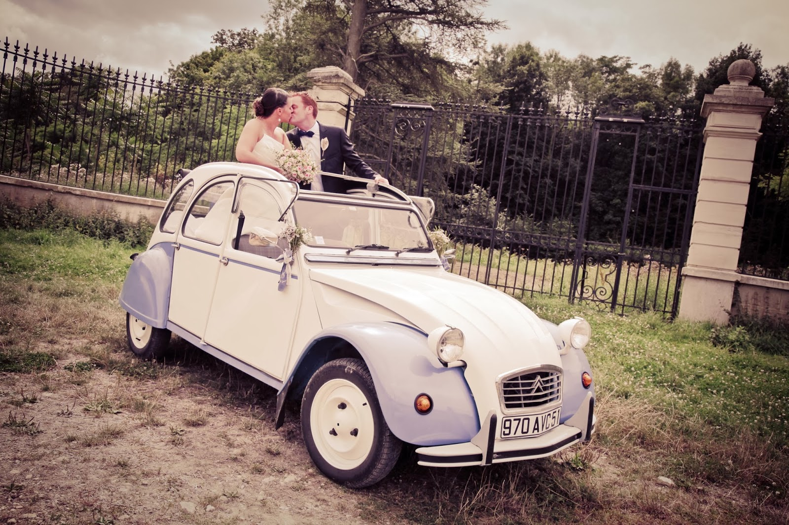Bride and groom in the 2cv, french vintage car - Wedding photography by Elisabeth Perotin