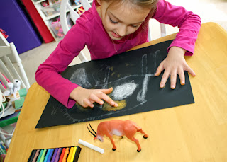 "After the glue dried and left an embossing of Tessa's antelope sketch, she ""colored"" in her design by rubbing and blending chalk with her fingers. She really enjoyed this part of the project."