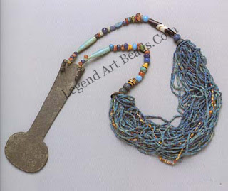 Menyet consisting of a thick necklace of faience, beads connected by two strings of glass and stone beads to a bronze counterpoise.
