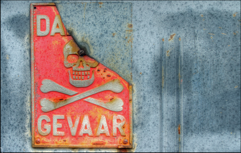 A damaged metal sign with the words Danger and Gevaar and an image of the Jolly Roger