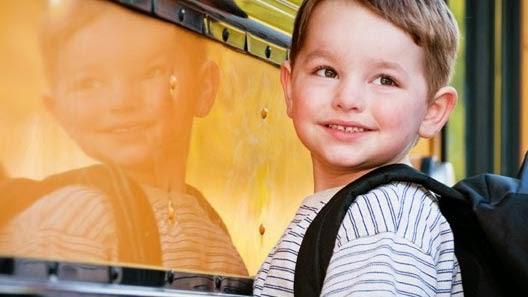 Criança com mochila ao lado de seu reflexo numa superfície plana vertical.