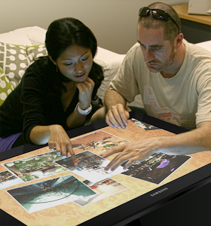 Two tourists explore content while sitting at a digital table.