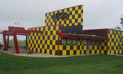 Yellow and dark brown checkered drive in restaurant with Porky's light bulb sign on the side