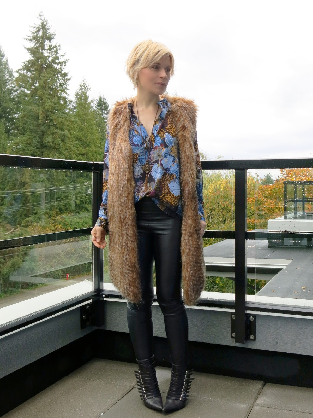 styling faux-leather leggings with a floral blouse, long furry vest, and rockerish booties
