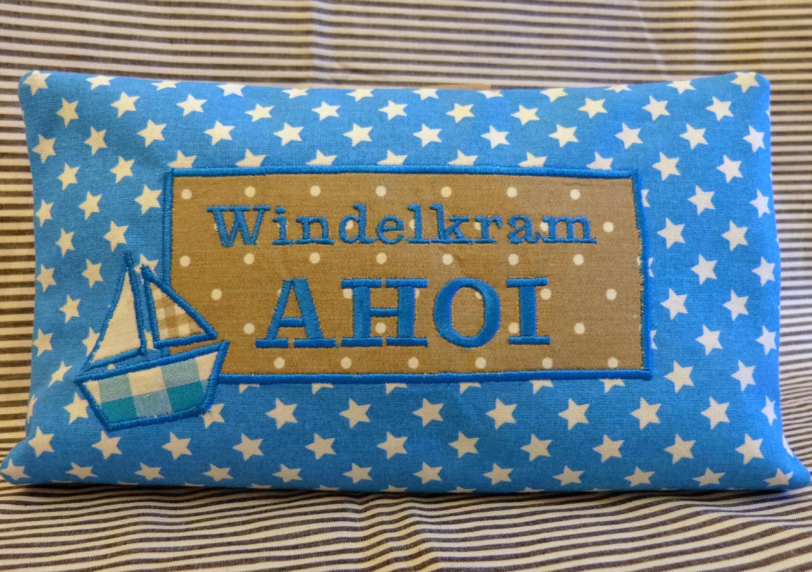 """fertige maritime Wickeltasche, türkisfarbener Sternenstoff außen, Schriftzug """"Windelkram AHOI"""" auf beigefarbenen Stoff mit Punkten, daneben eine kleine Schiffsapplikation"""