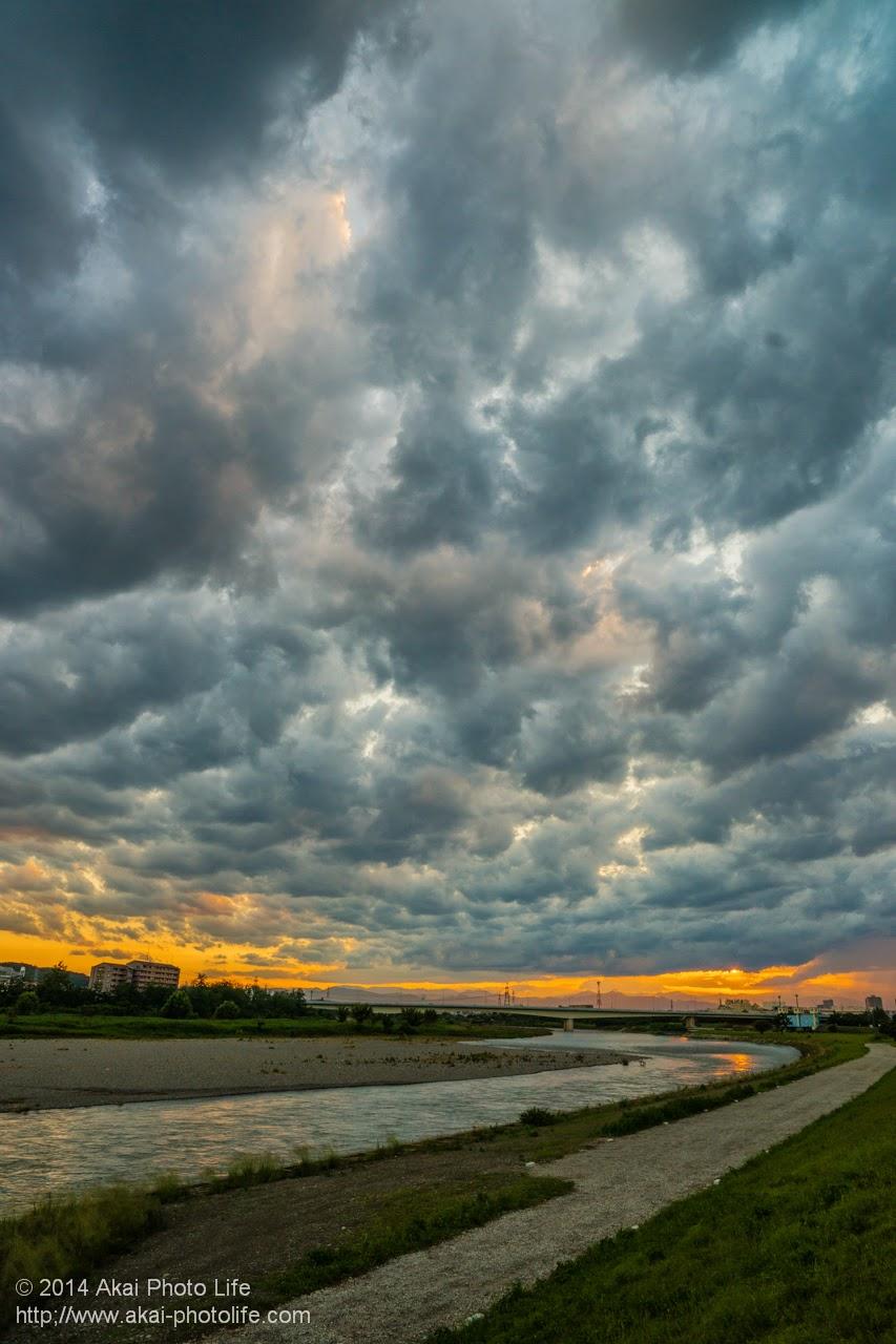 梅雨の雨雲と夕焼けが照らす多摩川