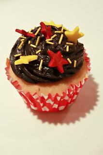 Cupcake with black buttercream swirl and red and yellow fondant stars