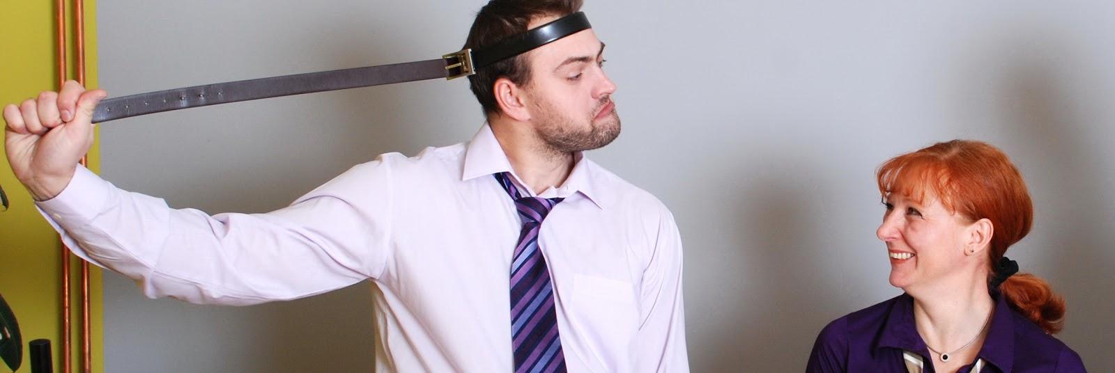 Pavel Kučera se sám tahá za pásek, který má obepnutý kolem hlavy a Radka Maňáková se mu směje