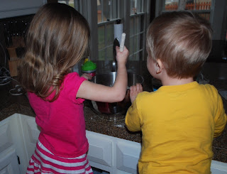 siblings making muffins together with protein powder