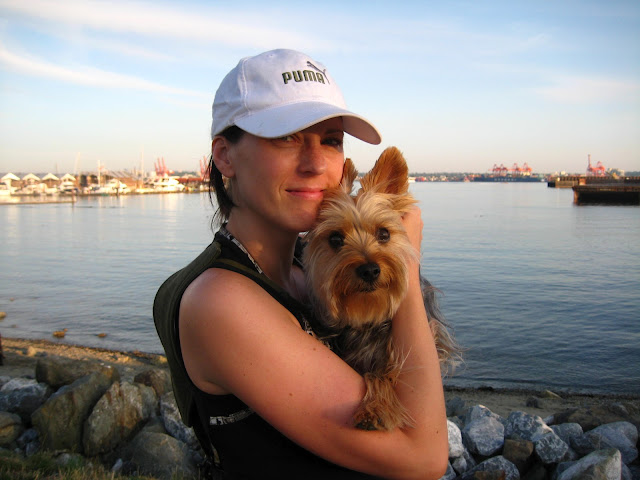 A woman holding a Silky Terrier puppy at the beach.