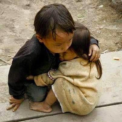 Foto de um garotinho nepalês abraçado à irmã. Ele tem aproximadamente quatro anos e ela dois anos e meio. Ajoelhado, com o tronco levemente inclinado à frente, ele apoia a mão direita no chão de tábua sobre base de demolição, o braço esquerdo envolve a irmã, sentada, aconchegada com o rosto afundado no peito dele, ela estende o braço e apoia a mão na cintura do irmão e encosta o pezinho descalço sob o joelho direito dele; a perna esquerda da garotinha está dobrada em V invertido, quase toda coberta pelo blusão bem maior que ela, em malha surrada que um dia foi clara, como a pele de ambos, suja pela poeira. O garotinho nepalês abrigado com casaco preto e calça jeans tem o olhar fixo no chão.