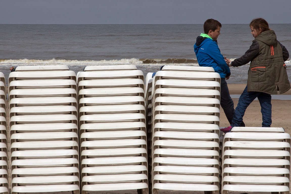 boy and girl playing on stack of beach chairs