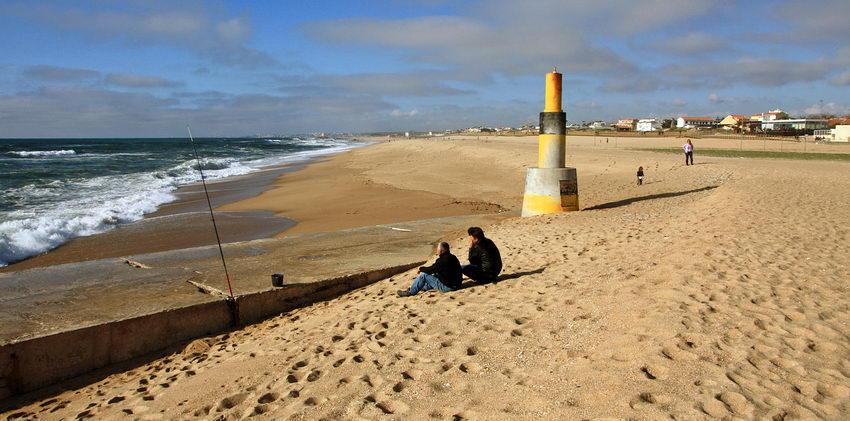 Foto de sul para norte. À esquerda o princípio do Quebra-mar com dois pescadores sentados e à direita o areal com uma mulher e uma criança