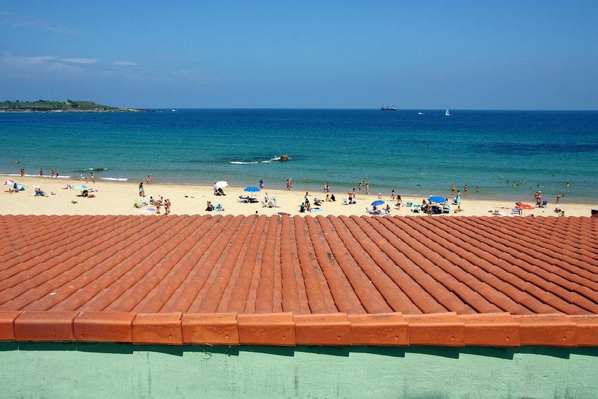 Foto da praia com alguns barcos ao longe e um telhado em promeiro plano