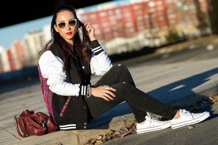 Look deportivo con chaqueta de beisbol, jeans rotos en las rodillas, Converse de piel y brazalete de Uno de 50