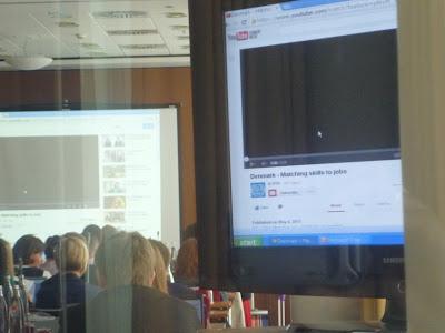 Angeschnitten ein Flachbildschirm, im Hintergrund Konferenzbesucher