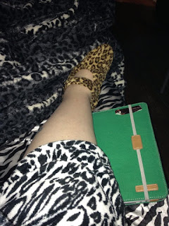 Author's pale leg with zebra satin sheets underneath, brown leopard print slipper, white leopard print bathrobe, white leopard print blanket, and green iPad case.