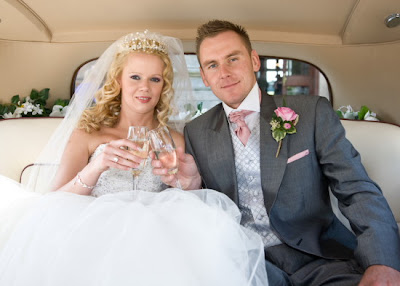 Newly weds have champagne in Rolls Royce