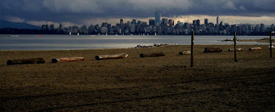View of sandy beach, sailboats and freighters on English Bay and downtown Vancouver under an overcast sky