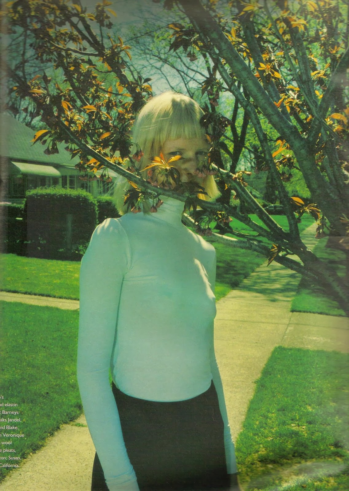 "Kirsten Owen by Mario Sorrenti in ""Suburban Outfitters"" for W Magazine, July 1998 - white turtleneck, tree-blossoms, springtime, black skirt, 90's fashion magazine photography, blonde bob with bangs, hiding behing a tree-branch, muted futuristic 90's feel, bra-less nipples, no bra"