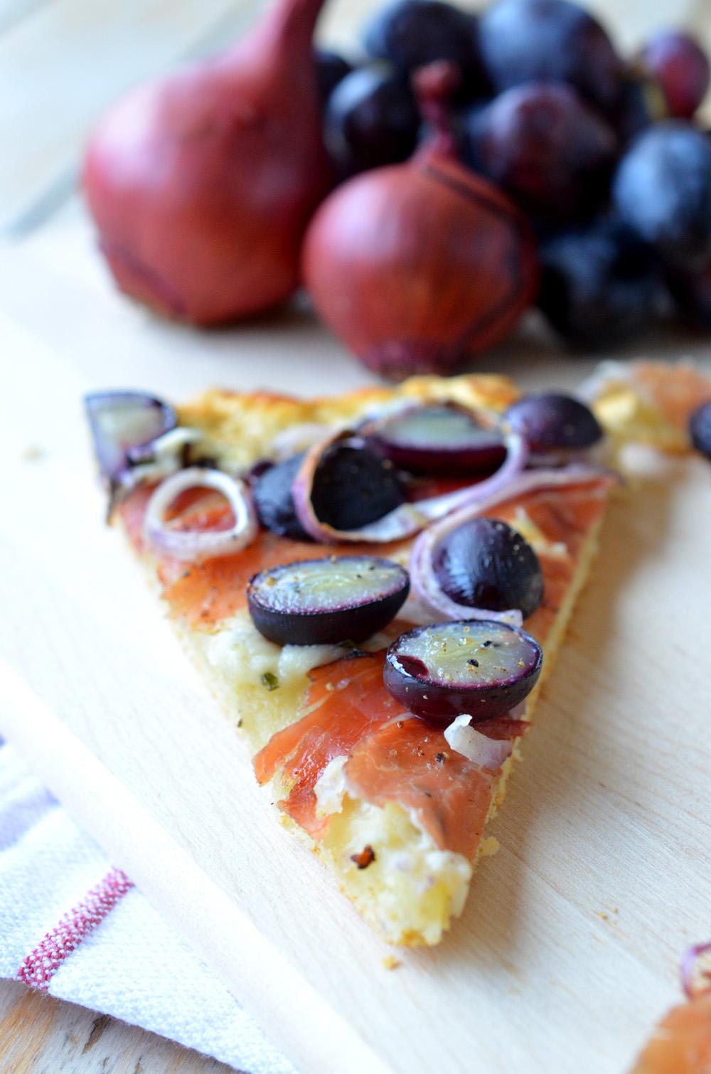 Pizza mit Kräuterquark, roten Zwiebeln, Trauben und Speck