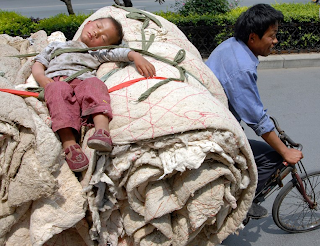 funny pictures Chinese child sleeping on the back of a bike