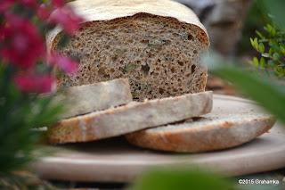 Chleb pszenny razowy, z ziarnami dyni i czarnuszki, wśród kwiatków