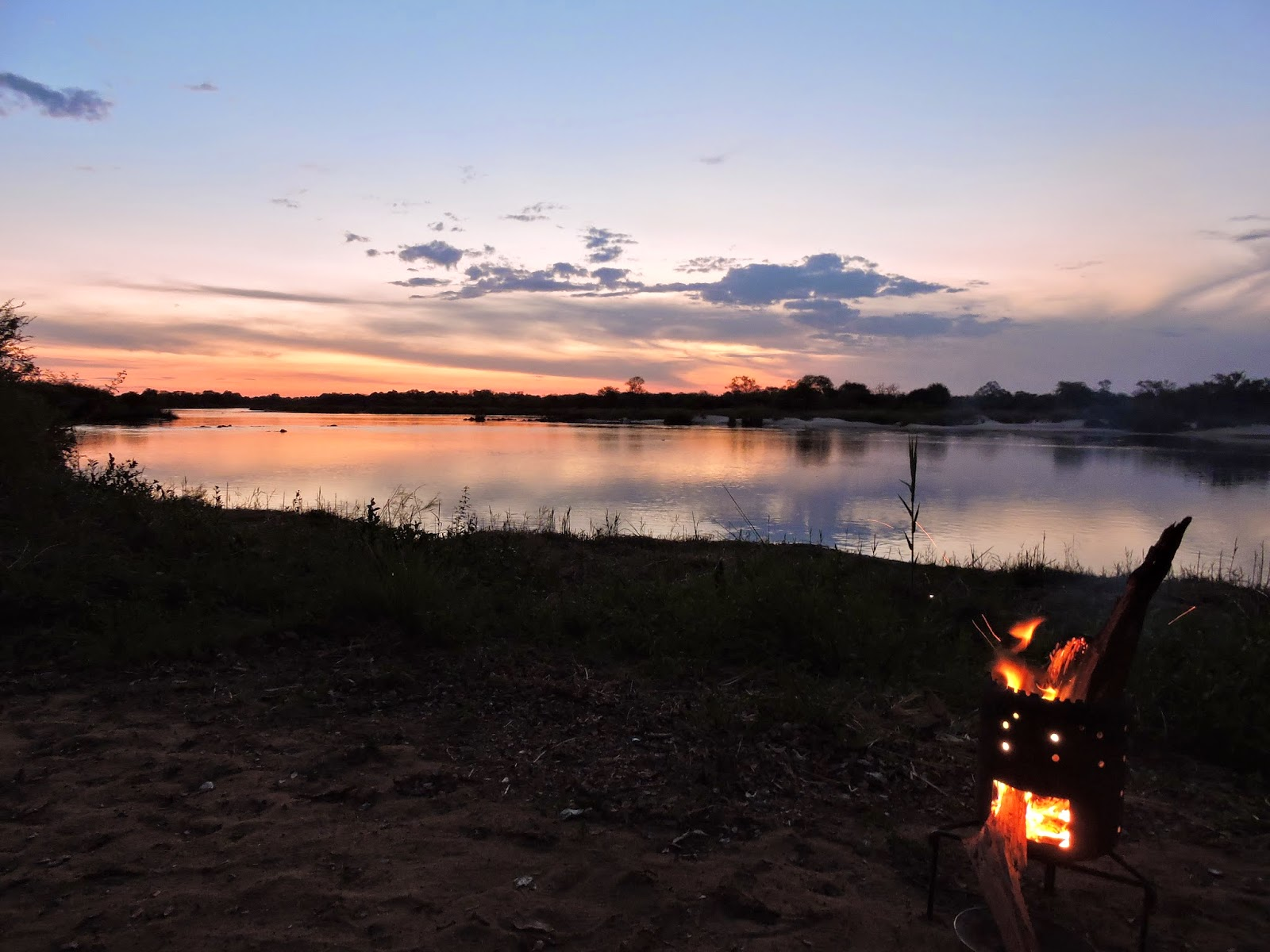The sun set over the Okavango River with our campfire visible nearby.