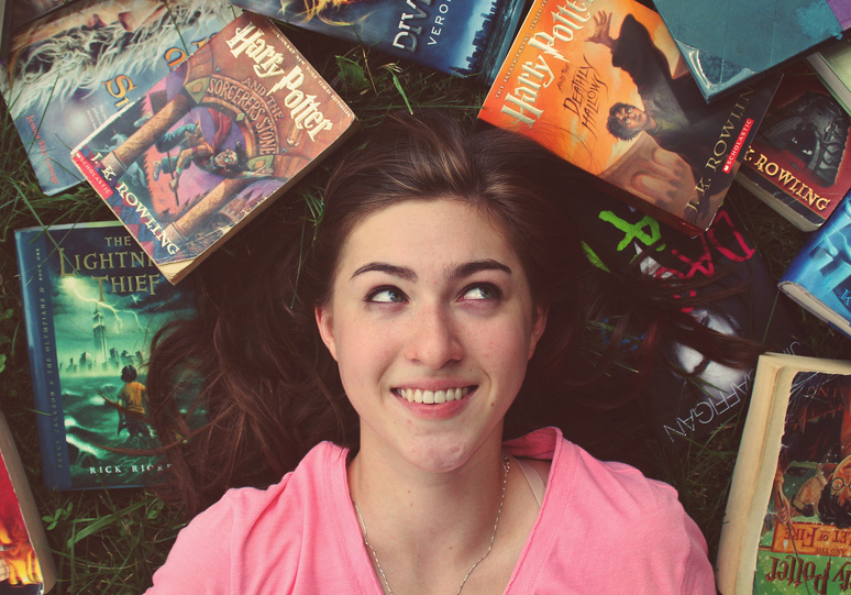 A smiling girl lying down surrounded by Harry Potter books