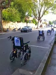 Line of empty wheelchairs parked in standard street side parking spaces in protest about handicapped parking