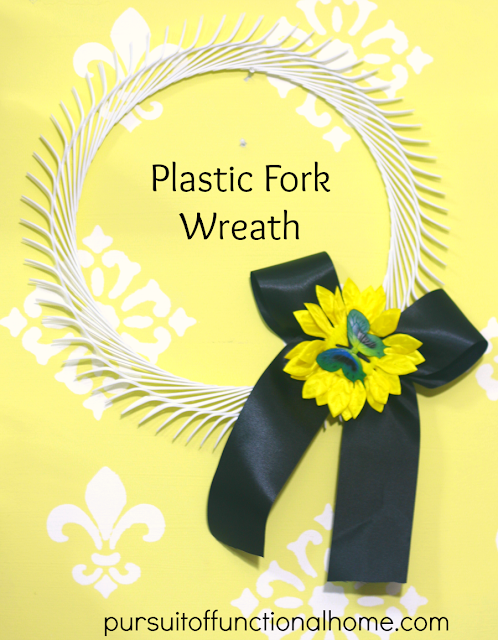 Plastic Fork Wreath with black ribbon, yellow daisy and butterfly