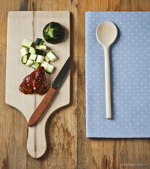 Zucchini getrocknete Tomaten Brettchen Messer Kochlöffel