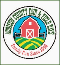 Circle logo for Addison County Fair & Field Days with a red barn in the middle