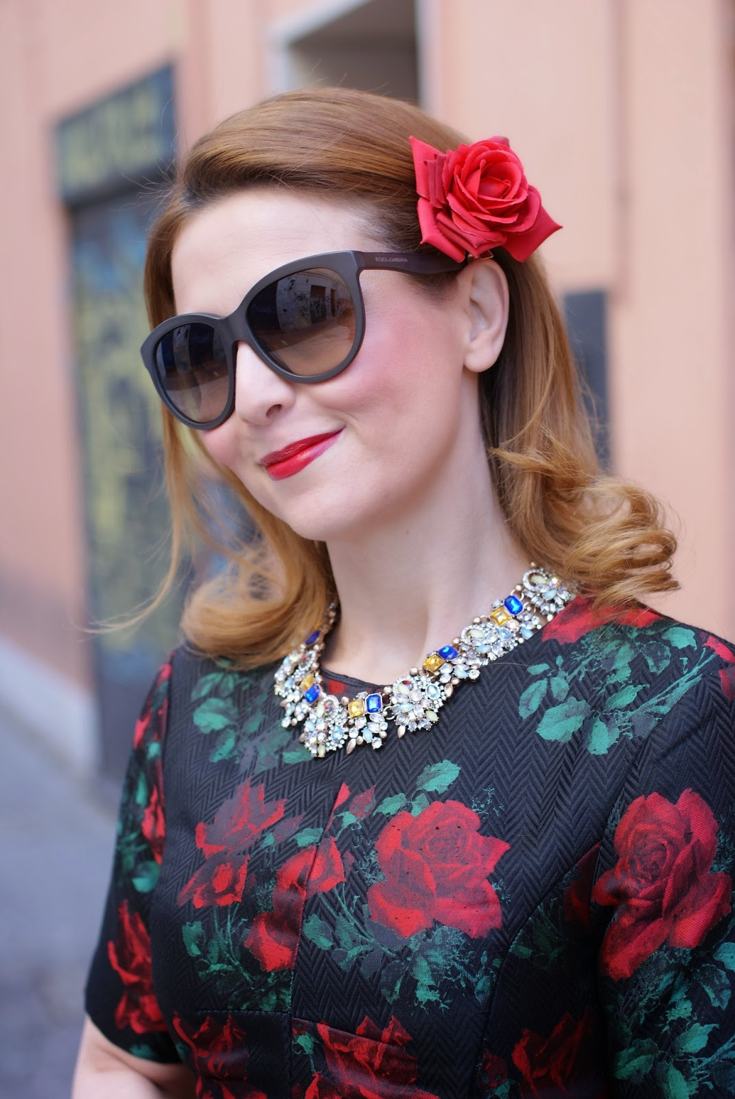 A red rose hairpin on my hair, a crystal encrusted necklace and red roses print