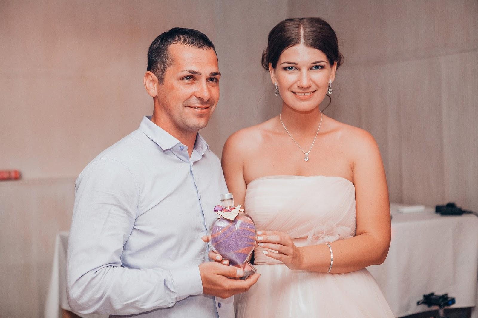 счастливые жених и невеста с сосудом песка